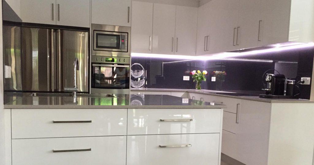 Glass splashback with under cabinet LED strip lighting.