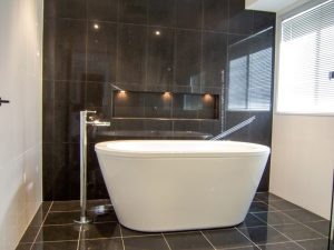 Gorgeous black & white bathroom with floor tile used a feature wall with decorative niche - bathroom renovation by Master Bathrooms & Kitchens.