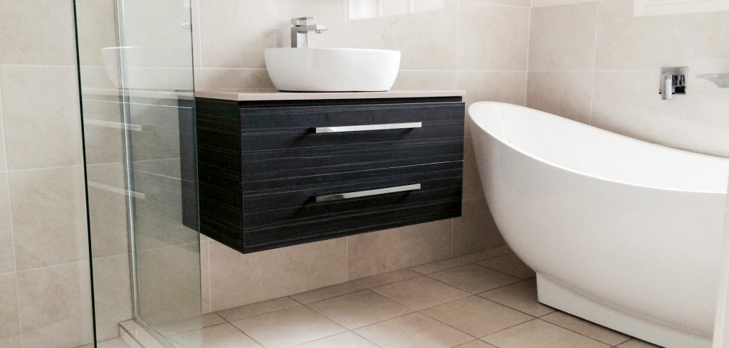 Stunning black wall hung vanity with white above counter bowl, white free standing bath with chrome tapware and fittings.