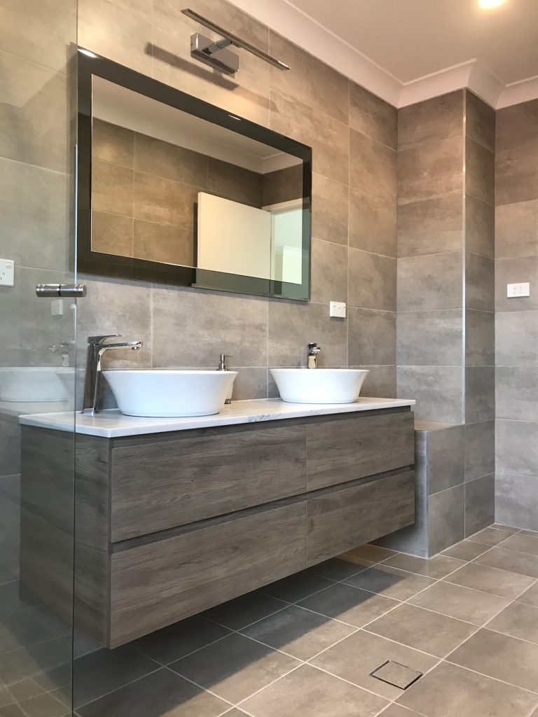 Gorgeous neutral colour schemed bathroom renovation with wall hung timber vanity and chrome tapware.