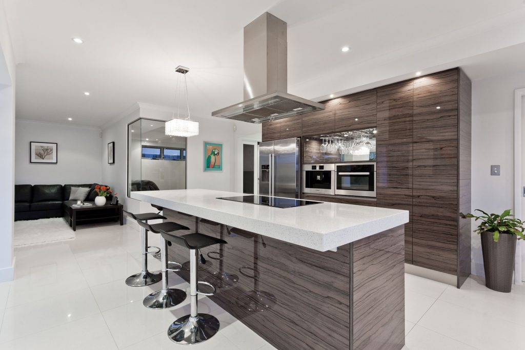 Open plan kitchen with dark neutral cabinets and white benchtops.