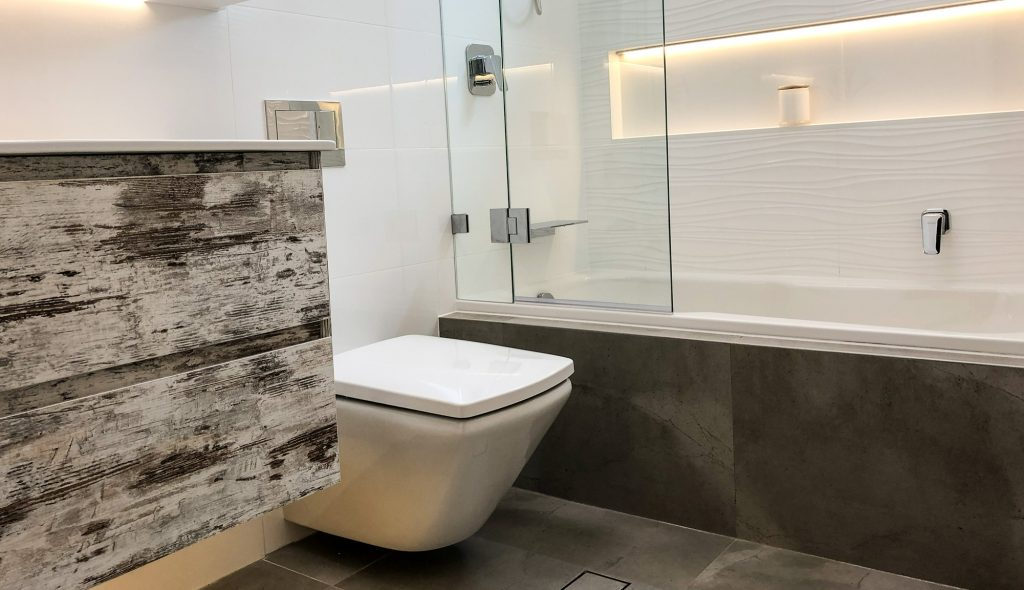 Stunning shower bath combination with LED lit niche, wall mount vanity, wall mount toilet and frameless glass shower screen
