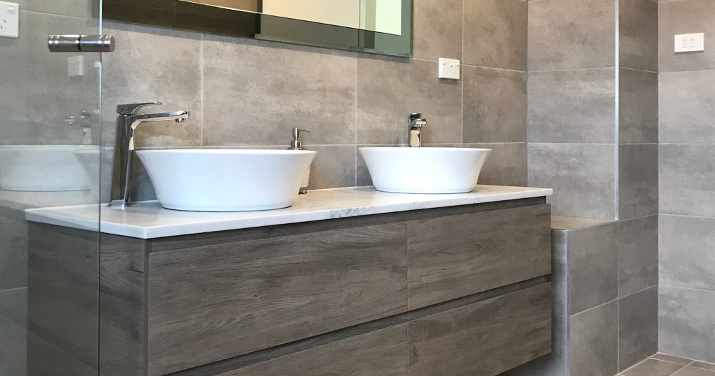 Single large mirror over double bowl vanity - bathroom renovation by Master Bathrooms & Kitchens.