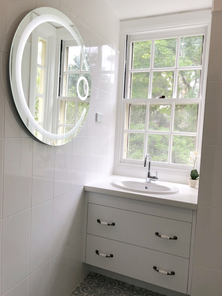 Gorgeous Round mirror with LED lighting and magnifier creates the perfect illumination for makeup application - bathroom renovation by Master Bathrooms & Kitchens.