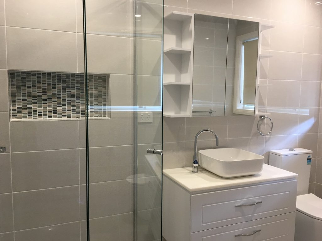 Mirrored wall cabinet with decorative shelving - bathroom renovation by Master Bathrooms & Kitchens.