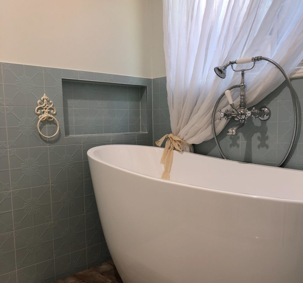 Modern free standing bath with antique tap fittings and built-in niche