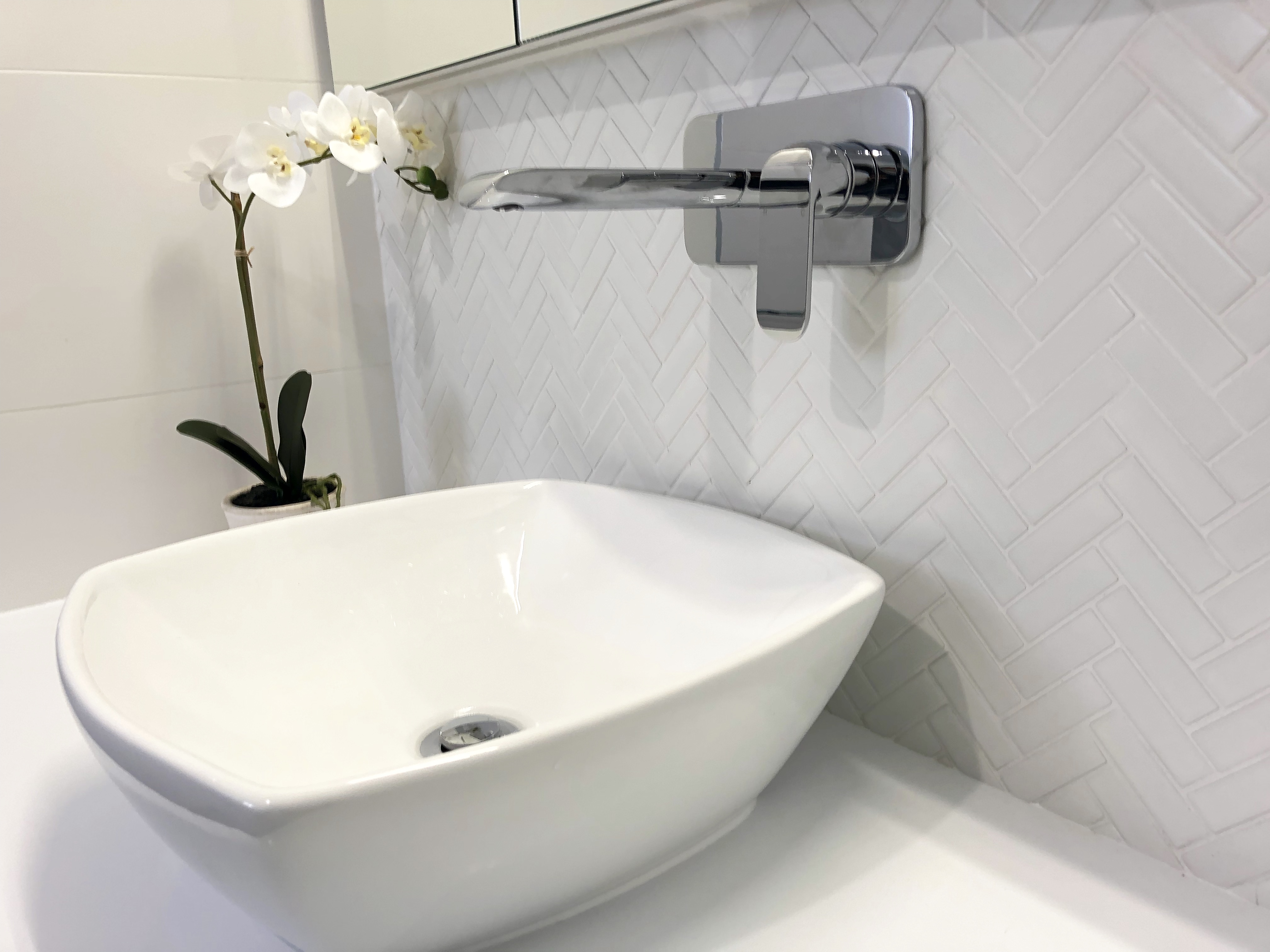 Gorgeous white herringbone tile adds character to this ensuite - bathroom renovation by Master Bathrooms & Kitchens.