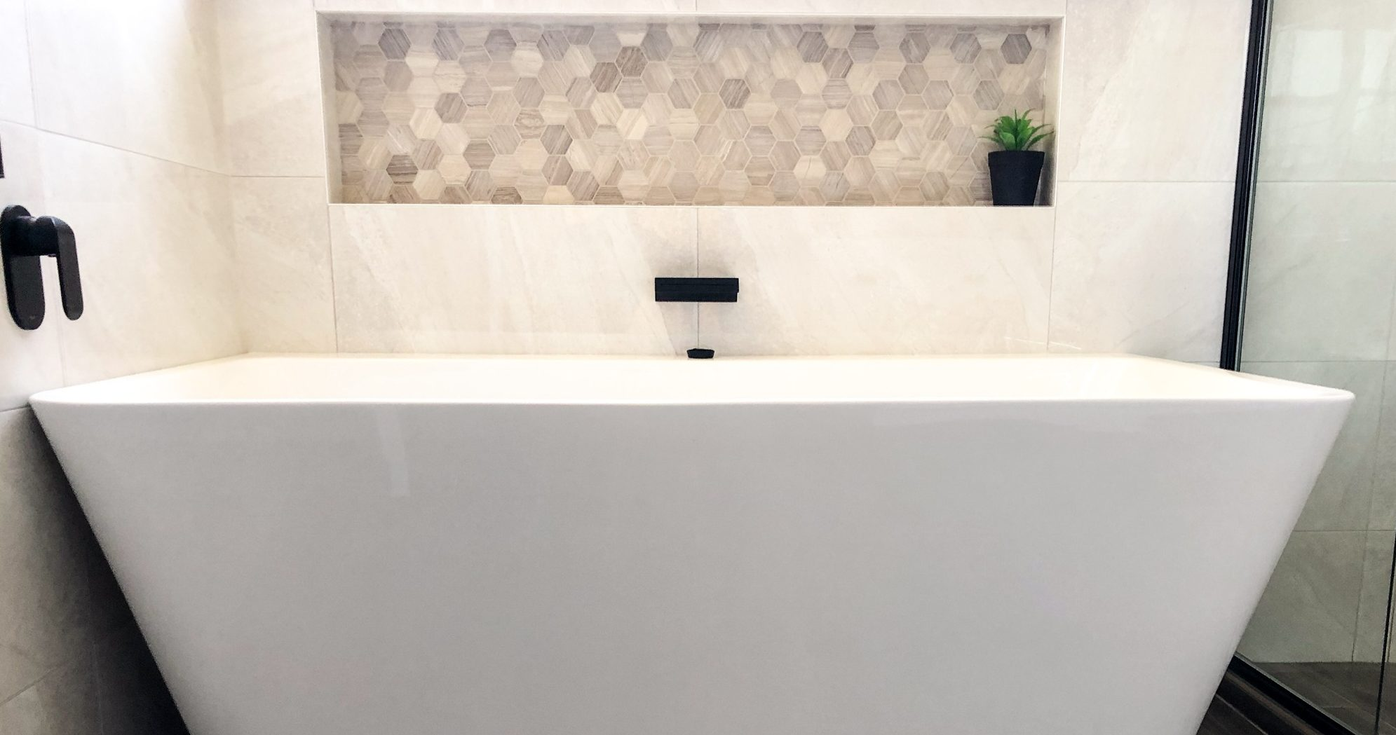 Gorgeous white wall faced free standing bath with decorative niche