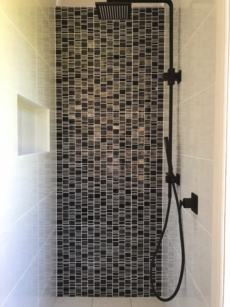 Feature wall in shower recess with rainfall shower head and adjustable hand held shower rose - bathroom renovation by Master Bathrooms & Kitchens.