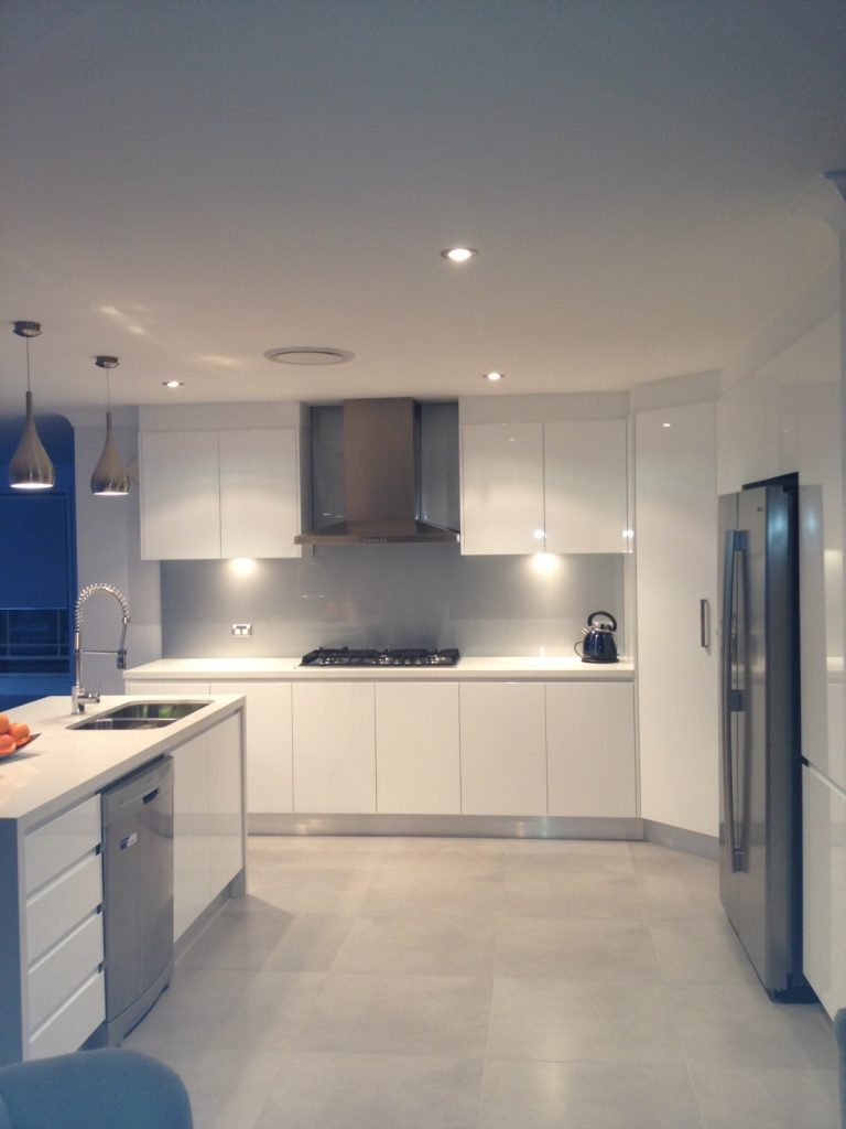 Stunning white polyurethane finger pull cabinets with engineered stone benchtops and stainless steel appliances.