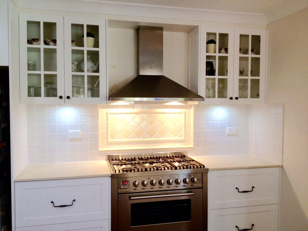 Gorgeous white shaker cabinets with engineered stone benchtops, stainless steel appliances and tiled splashback.