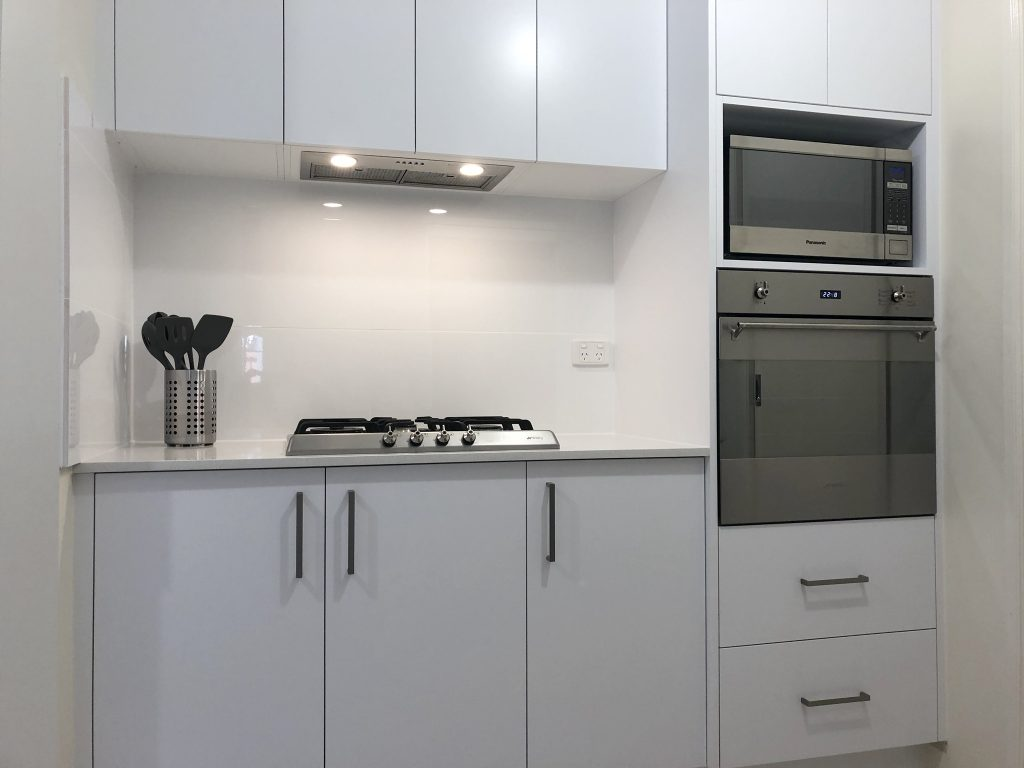 Stainless steel gas cooktop and extractor fan, wall oven and microwave with tiled splashback.