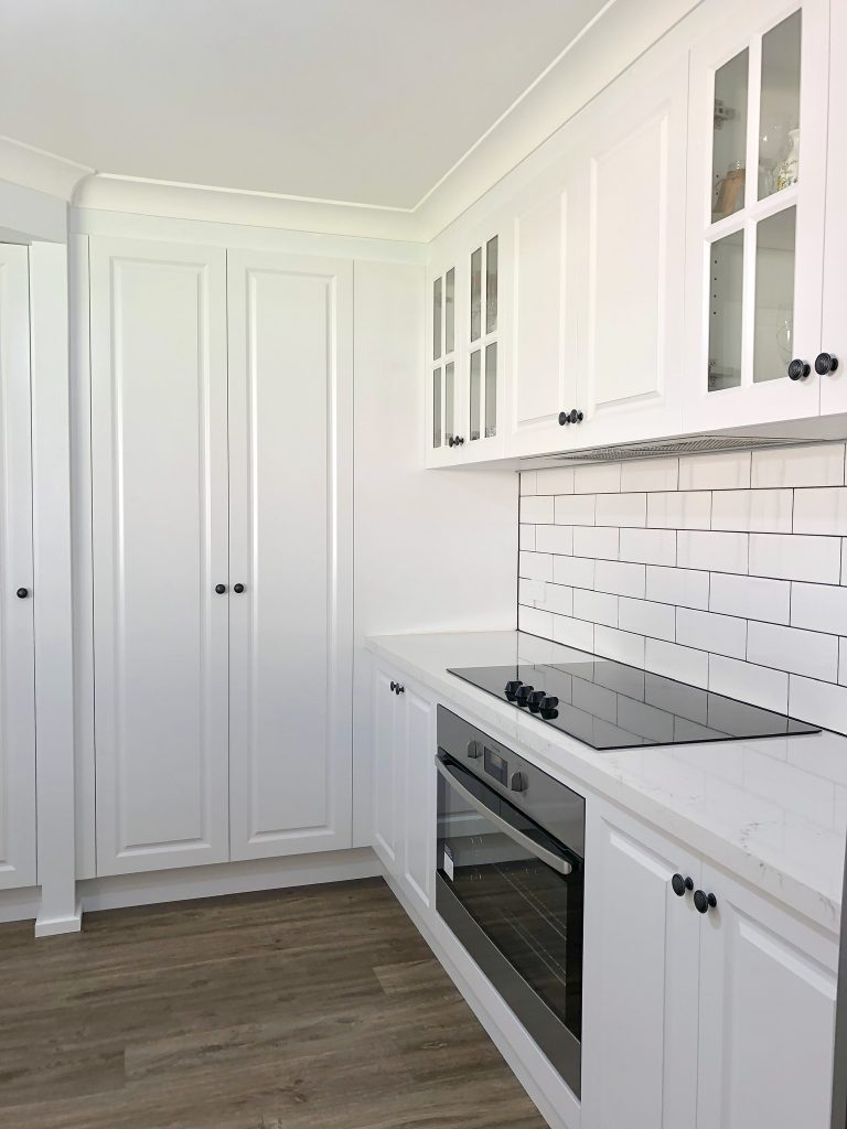 Gorgeous white polyurethane cabinets wth 3 door pantry and timber floors - kitchen renovation by Master Bathrooms & Kitchens
