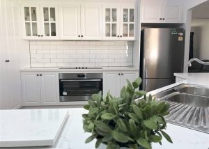 Stunning white shaker cabinets with Caesarstone benchtops and stainless steel appliances - kitchen renovation by Master Bathrooms & Kitchens.