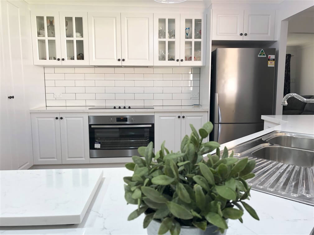 Stunning white raised panel cabinet doors with Caesarstone benchtops & subway tile - kitchen renovation by Master Bathrooms & Kitchens