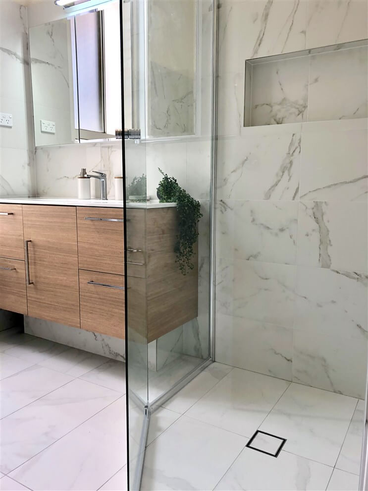 Stunning marble look alike porcelain tiles, shower niche & smart waste.Bathroom renovation by Master Bathrooms & Kitchens.
