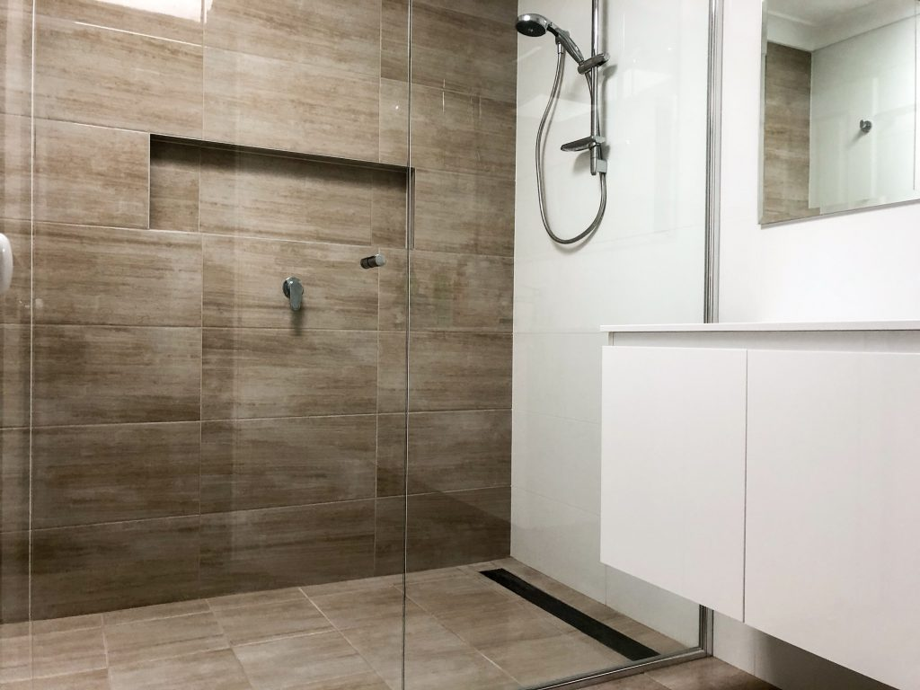 Beautiful shower recess with timber tile feature wall, shower niche, linear shower grate and semi-frameless shower screen - bathroom renovation by Master Bathrooms & Kitchens.