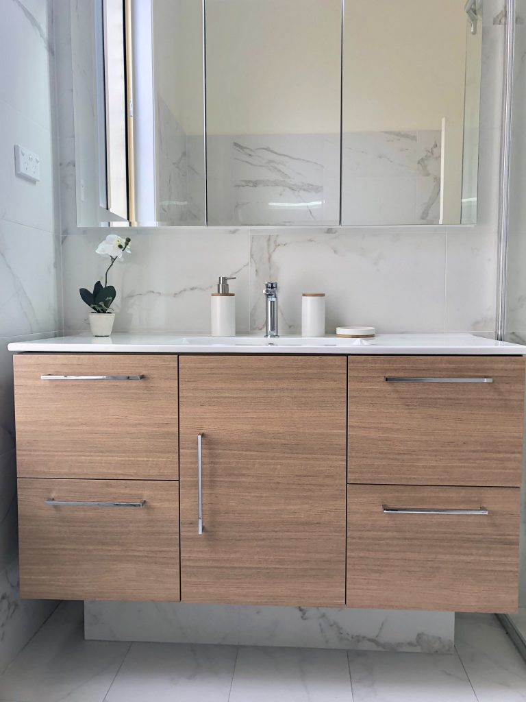 Gorgeous timber look vanity with custom made recessed mirrored shaving cabinet & faux marble porcelain tiles - bathroom renovation by Master Bathrooms & Kitchens
