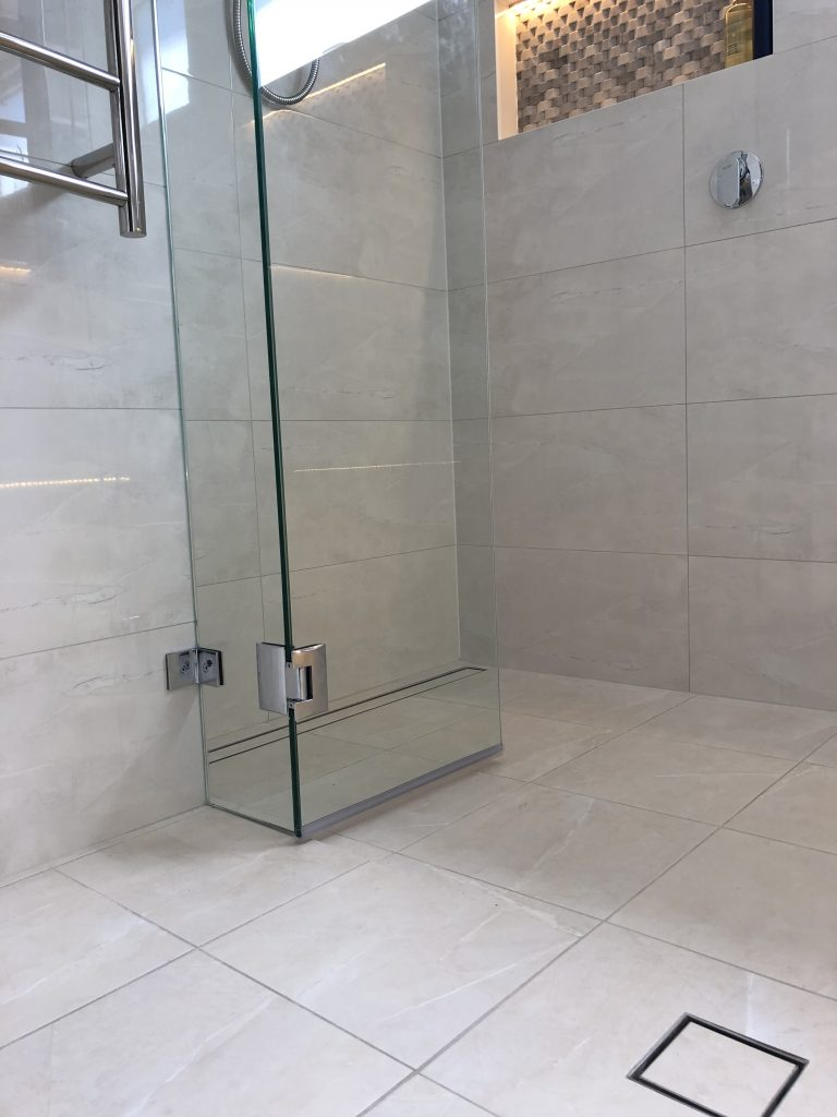 Stunning hobless shower featuring linear shower grate, frameless shower screen with pivot door an niche with LED strip lighting - bathroom renovation by Master Bathrooms & Kitchens.
