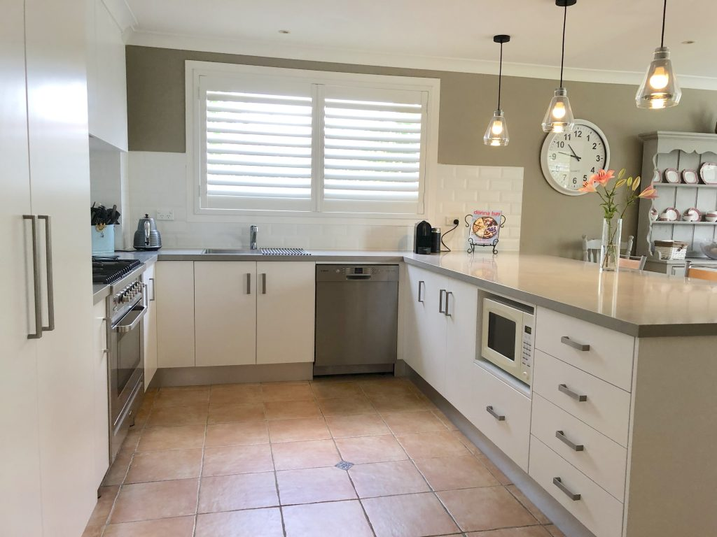 U shaped kitchen with lovely neutral colour scheme with pendant lights - kitchen renovation by Master Bathrooms & Kitchens.