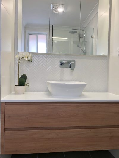 Stunning custom made timber vanity with stone benchtop, herringbone tile and custom shaving cabinet - bathroom renovation by Master Bathrooms & Kitchen.