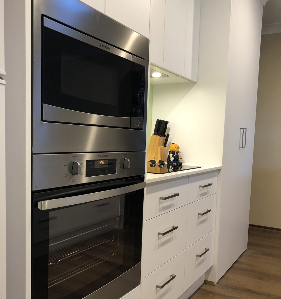 Single wall kitchen with white & tall wall cabinets to create the appearance of space and take advantage of storage - Kitchen Renovation by Master Bathrooms & Kitchens.