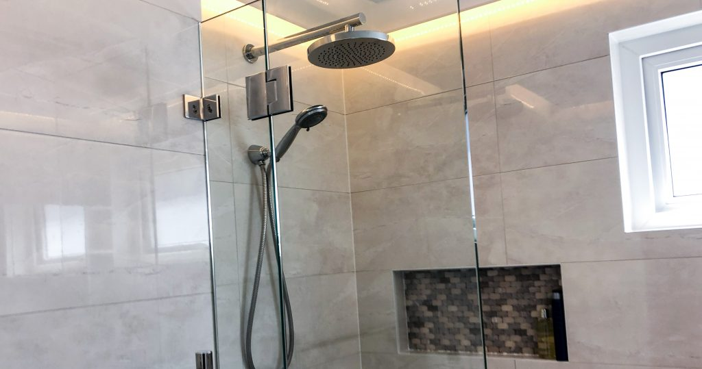 Beautiful chrome rainfall shower with hand held shower rose, shower niche and feature lighting in drop down ceiling - bathroom renovation by Master Bathrooms & Kitchens.