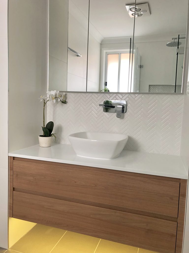Beautiful custom made timber vanity with above counter bowl, stone benchtop, herringbone tile, wall mounted tap and custom shaving cabinet - bathroom renovation by Master Bathrooms & Kitchens.
