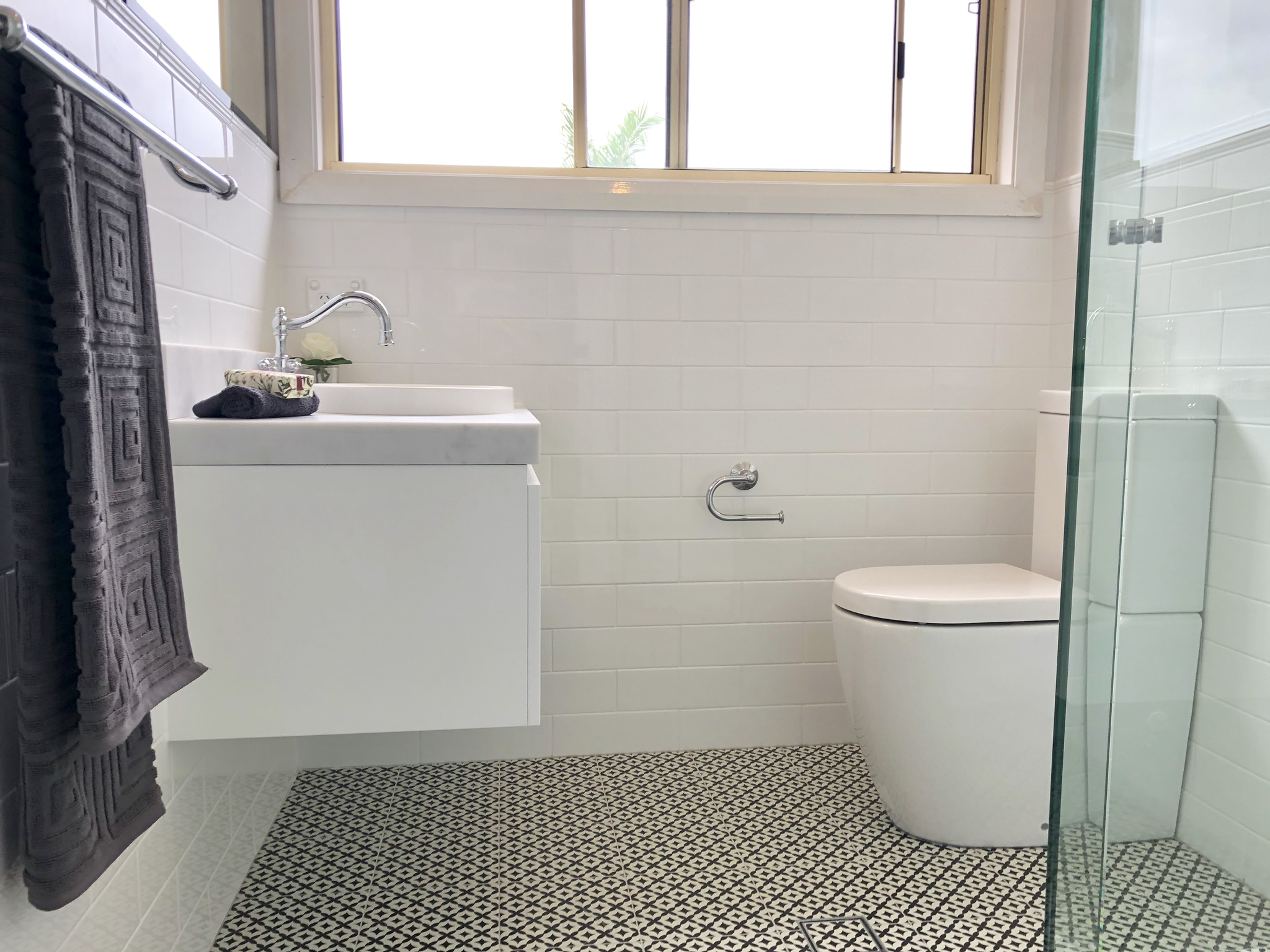 Gorgeous wall hung vanity, antique style tapware & fittings with subway wall tile and feature floor - bathroom renovation by Master Bathrooms & Kitchens.