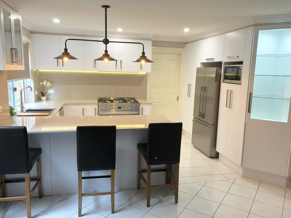 White cabinets, engineered stone benchtops & splashback & stainless steel appliances - kitchen renovation by Master Bathrooms & Kitchens.