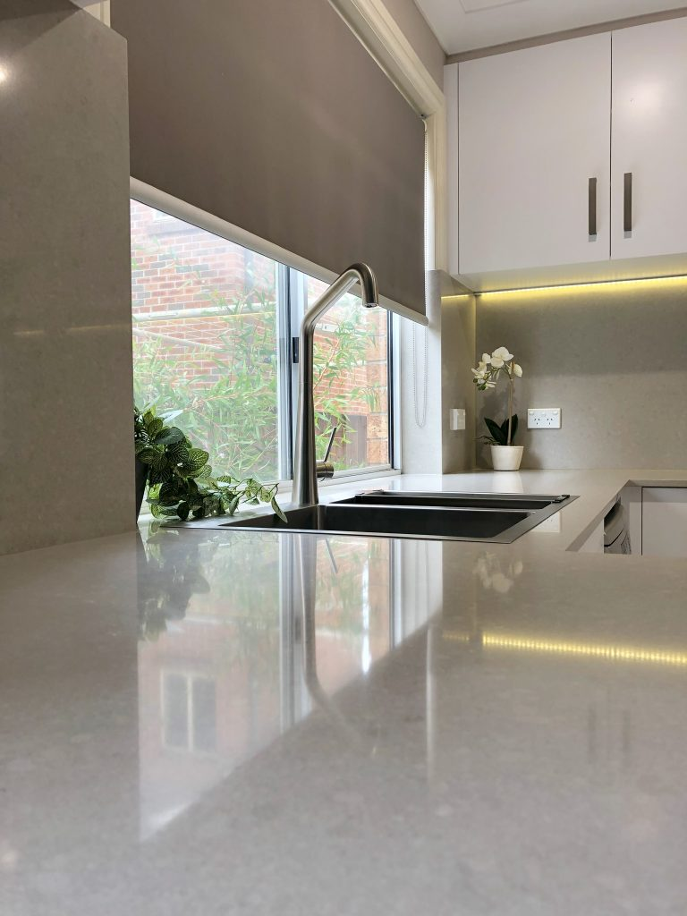 Beautiful engineered stone benchtop and splashback with flushmount brushed stainless steel sink and mixer tap - kitchen renovation by Master Bathrooms & Kitchens.