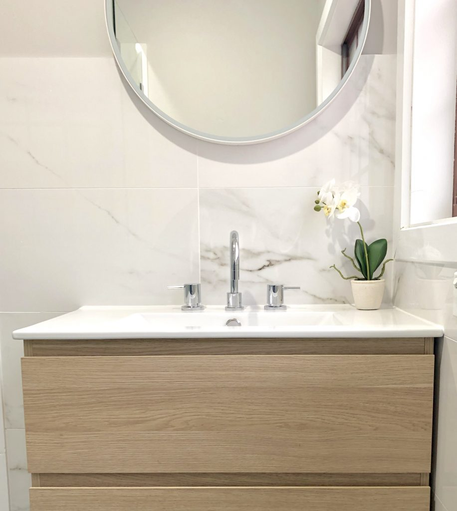 Gorgeous faux marble tiles with timber wall hung vanity and round mirror - bathroom renovation by Master Bathrooms & Kitchens.