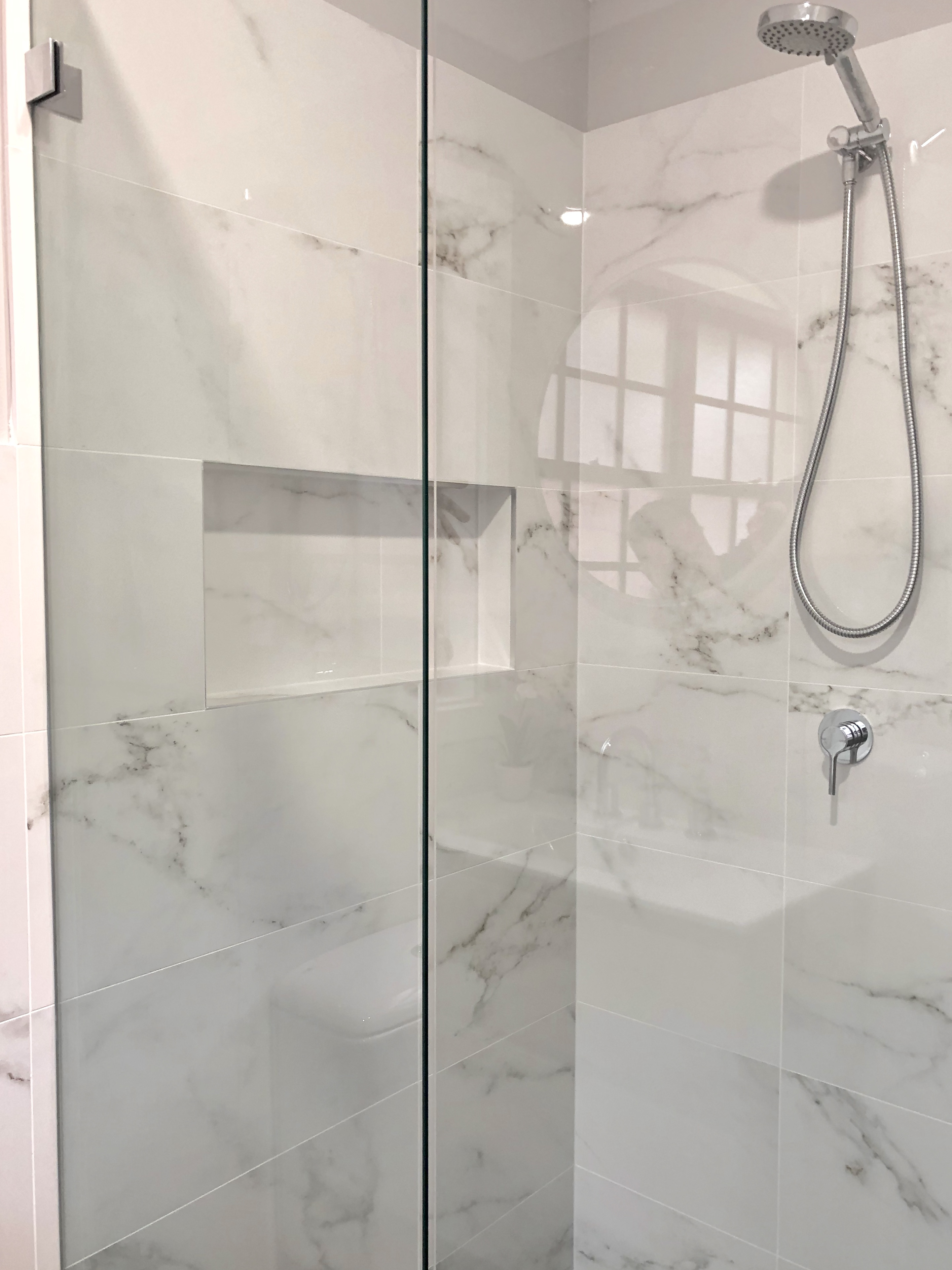 Corner shower recess with hand held shower rose, mixer, niche and frameless shower screen - bathroom renovation by Master Bathrooms & Kitchens.