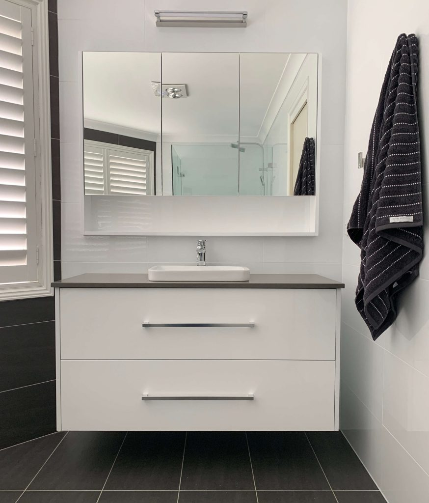 Gorgeous custom wall mount vanity with stone top and custom 3 door mirrored wall cabinet - bathroom renovation by Master Bathrooms & Kitchens.