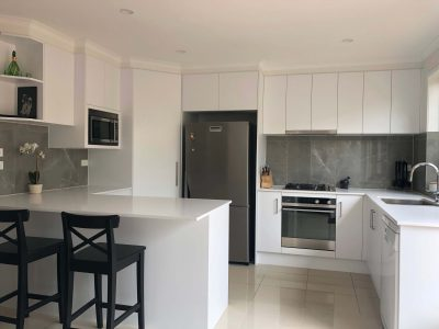 Stunning white acrylic cabinets with Caesarstone benchtops, tiled splashback and stainless steel appliances- kitchen renovation by Master Bathrooms & Kitchens.