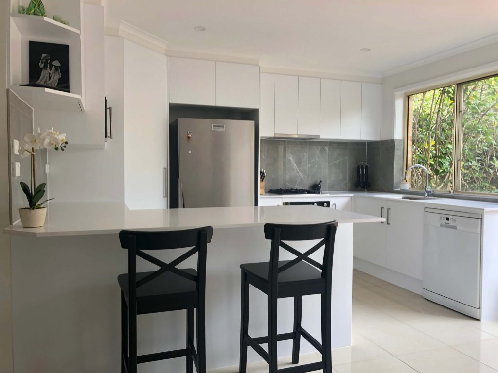 White acrylic cabinets with Caesarstone benchtops, tiled splashback and stainless steel appliances - kitchen renovation by Master Bathrooms & Kitchens.