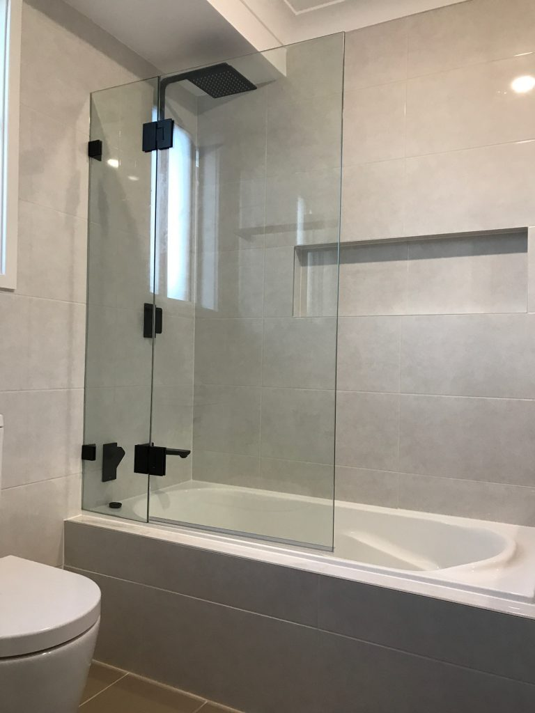 Gorgeous shower bath combination with black rainfall shower, recessed shower niche and pivot frames less shower screen - bathroom renovation by Master Bathrooms & Kitchens.