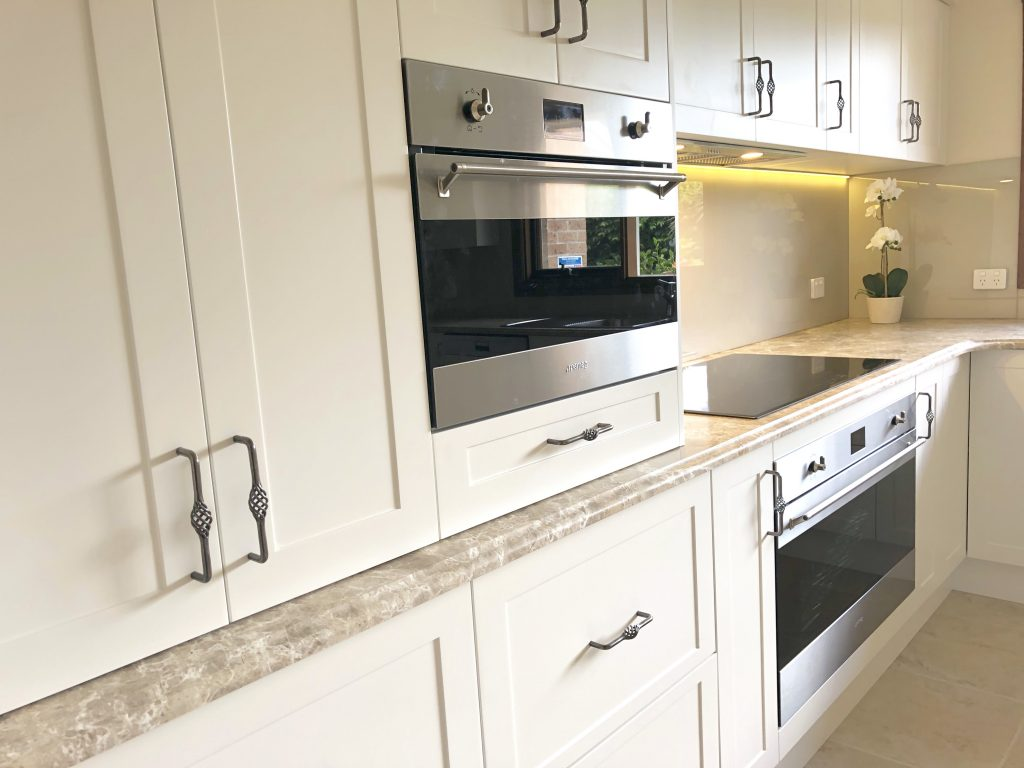 Modern induction cooktop set in stunning marble benchtop - kitchen renovation by Master Bathrooms & Kitchens.