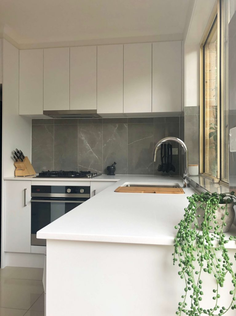 Stunning tiled splashback using faux marble 300 x 600mm porcelain rectified tile and beautiful undermount sink with arc mixer tap - kitchen renovation by Master Bathrooms & Kitchens.