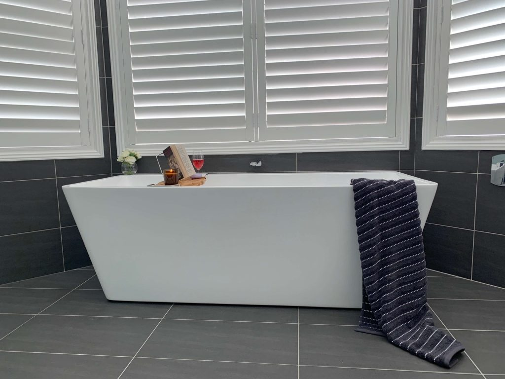Stunning white back to wall free standing bath contrasting perfectly with the dark porcelain tiles - bathroom renovation by Master Bathrooms & Kitchens.